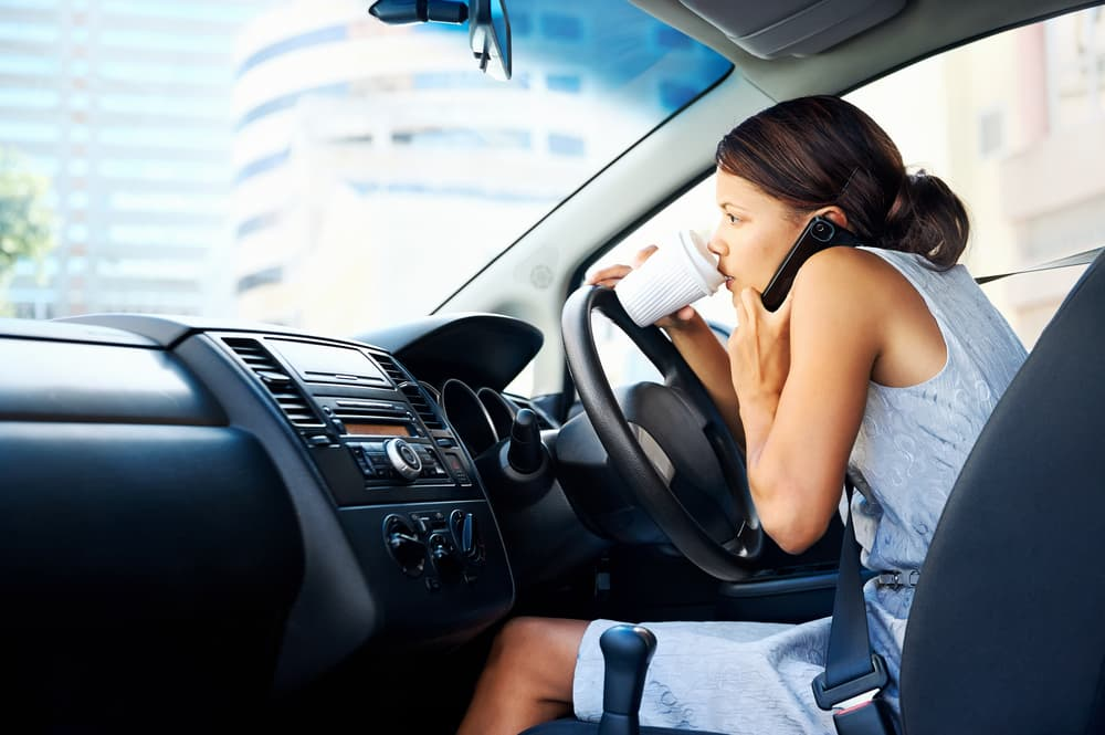 woman drinking coffee distracted while driving
